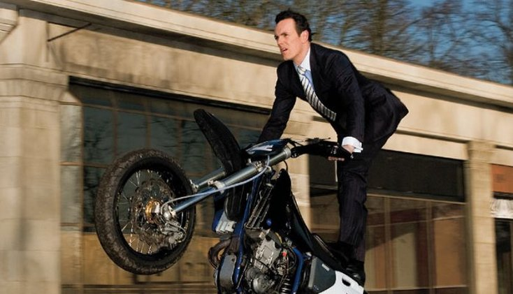 Man in suit performing a wheelie on a motor bike